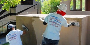 Stucco workers applying stucco to a wall